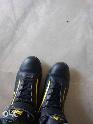 Pair Of Black And Yellow Leather Boots