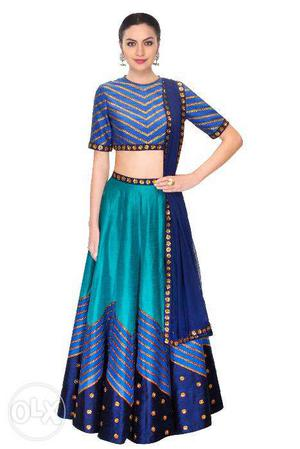 A Teal blue raw silk lehenga with printed lines and navy