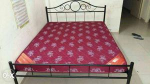Red And White Quilted Mattress And Black Metal Bed Frame