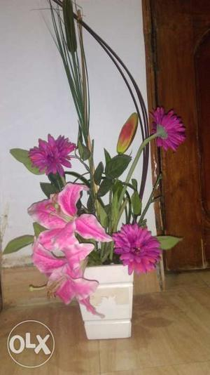White plastic vase with artificial pink flowers