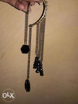 1 eair clufs in black colour and wrist watch