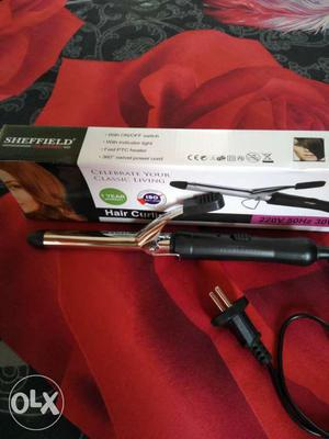 A brand new Silver And Black Hair Iron Curler with one year