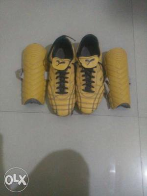 Pair Of Yellow Cleats And Pair Of Yellow Shin Guard