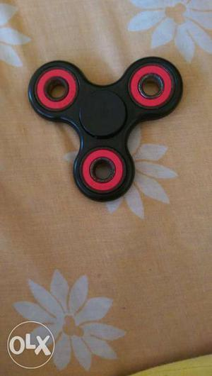 Black and red fidget spinner in case
