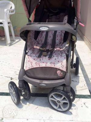 Baby's Black And Gray Graco Stroller With Feeding Table