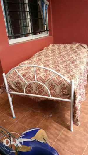 Single iron bed with plywood on top