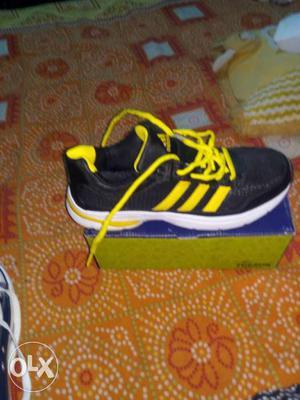 Black And Yellow Adidas Athletic Shoe On Box