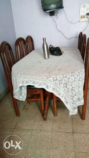 White Floral Table Cloth; Brown Wooden Table And Chairs