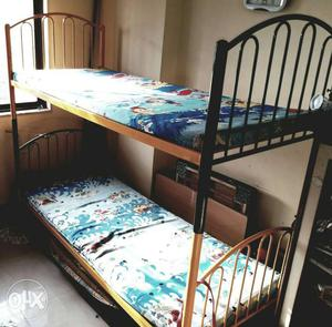 Green and yellow bunk beds with mattresses. Size