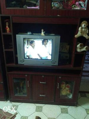 Grey Widescreen CRT TV And Brown Wooden TV Hutch