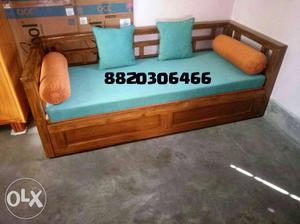 Brown Wooden Daybed With Teal Mattress, Two Throw Pillows