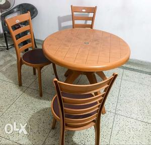 Round Brown Plastic Table With Three Chairs