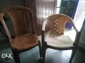 Two Beige And White Plastic Chairs with folding table.