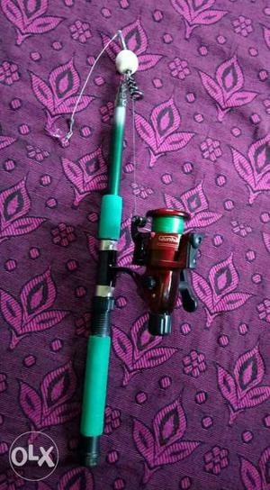 Green And Black Fishing Rod With Fishing Reel